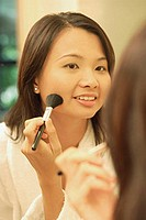 Woman putting on make-up with a blush brush