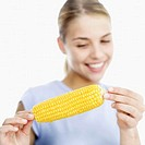 close-up of a teenage girl holding a corncob