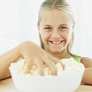 portrait of a girl with her hand in a bowl of popcorn
