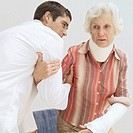 male doctor helping a senior woman out of a wheelchair