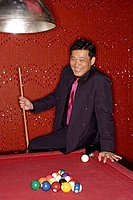 Man with pool cue leaning on table.