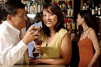 Couple having drinks, woman looking at camera