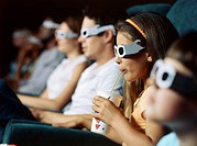 Row of people in a movie theatre wearing 3D glasses
