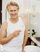Portrait of a mid adult man holding a toothbrush and smiling