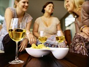 Low angle view of three young women sitting and chatting with wine and snacks
