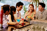Young adults at bar counter having drinks