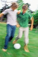 Two young man playing soccer in a park