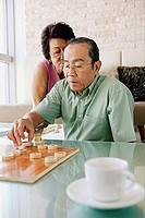 Senior man playing Chinese chess, wife behind him