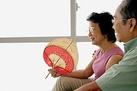 Senior couple sitting down, woman holding fan