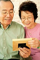 Mature couple, looking at picture frame