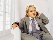 Boy sitting in a chair and talking on a mobile phone, pretending to be a businessman