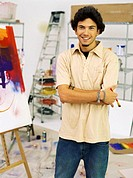 Close up of a young man standing and holding a paint brush