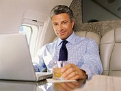 Close-up of a businessman sitting in a airplane working on a laptop