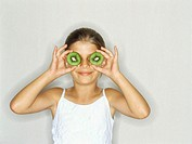 Close-up of a girl holding kiwi slices in front of her eyes