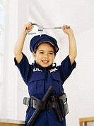 Close-up of a girl pretending to be a policewoman and holding a pair of handcuffs
