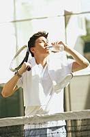 Man with tennis racket, drinking from water bottle