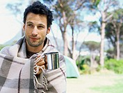 Close-up of a young man holding a mug wrapped in a blanket