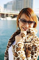 Young woman wearing sunglasses and fur coat