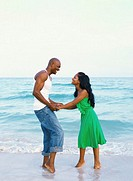 Side view of a young couple standing on the beach