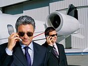 Two businessmen talking on mobile phones
