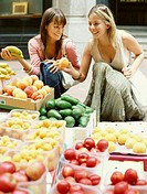 Two young women looking at fruit