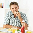 Portrait of a young man sitting at a dinner table eating a French fry