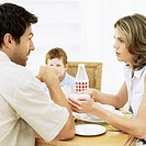 Young woman giving a bowl to a young man at the breakfast table with a young boy (8-10) sitting across