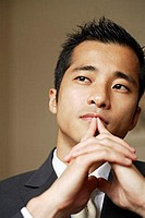 Businessman with hands clasped, fingers on mouth
