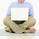 Young man sitting on the floor with legs crossed using a laptop