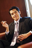 Young businessman holding cigar and glass of whiskey, looking away
