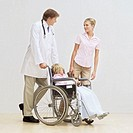 Male doctor pushing a young girl (8-10) in a wheelchair with a young woman walking beside her