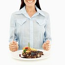 Young woman holding a fork and knife next to a plate of sliced meat with garnish and sauce