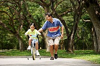 Father and daughter in park, daughter cycling, father running alongside her
