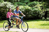 Couple riding tandem bicycle in park