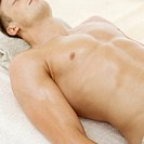 Young man lying on a towel