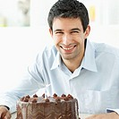 Portrait of a man smiling holding a chocolate birthday cake