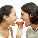 Side profile of a young couple sharing a doughnut