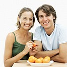 Portrait of a young couple with a bowl of oranges