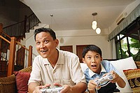 Father and son, sitting on sofa, playing with video games