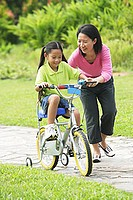 Daughter cycling, mother guiding her