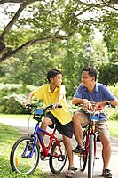 Father and son on bicycle, looking at each other