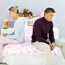 Young couple sitting back to back on the edge of their daughter´s (5-6) bed