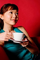Woman holding cup and saucer, looking away