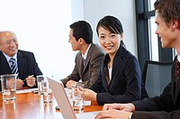 Businesswoman in meeting, turning to smile at camera