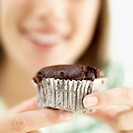 Close-up of a chocolate muffin in a teenage girl´s (15-17) hands (blurred)