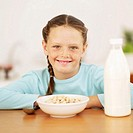 Portrait of a young girl (8-10) sitting behind a bowl of cereal and a bottle of milk