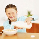 Young girl (8-10) pouring milk into bowl of cereal (blurred)