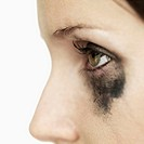 Close-up of the eye of a woman with mascara smeared under her eye