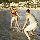 Young couple splashing water at each other at the beach