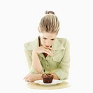 Young woman looking at a muffin on a plate